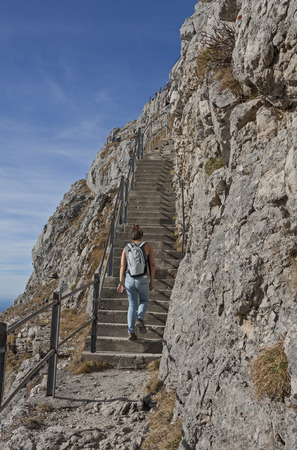 stepped: mountaineering young woman, climbing up a stepped road in the bavarian alps. Tourist attraction at wendelstein mountain. Stock Photo