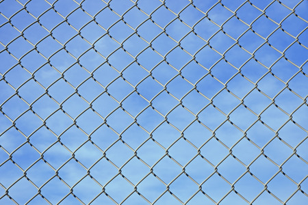 meshwork: mesh wire fence background against blue sky