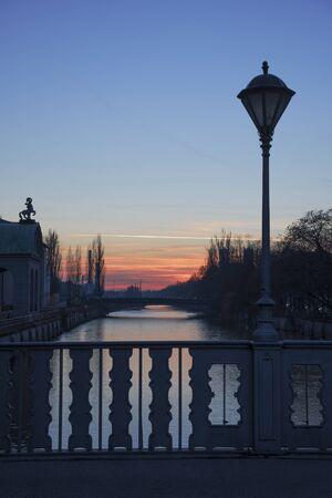 landschap: brug over de rivier de Isar münchen met oude lantaarn, zonsondergang landschap
