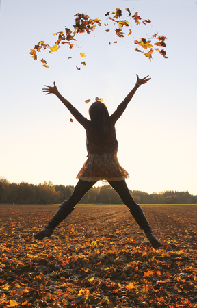 Jumping teenage girl, throwing leaves up in the air, autumnal fields.