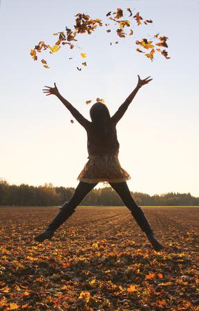 Jumping tienermeisje, gooien bladeren in de lucht, herfst velden. Stockfoto