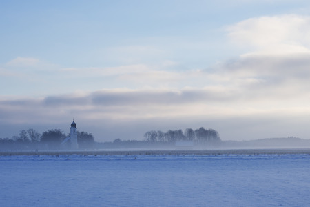 january sunrise: snowy field in rural winter landscape with village church on a foggy morning Stock Photo