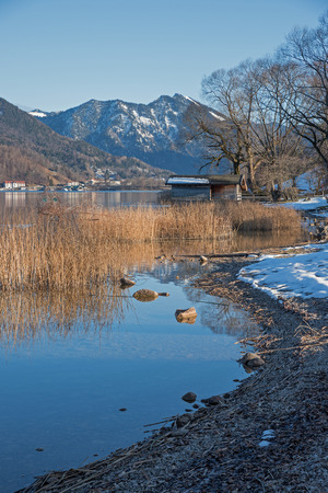 upright format: idyllic lake shore tegernsee with boathouse, at the end of winter, bavarian landscape. Upright format.