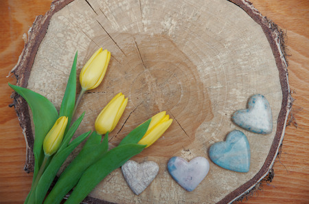 soapstone: rustic wooden background, yellow tulips and stone hearts on a tree slice, valentines or mothers day background Stock Photo