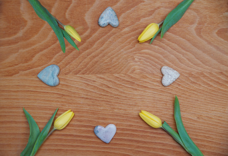 soapstone: red stained wooden background with yellow tulips and soapstone hearts Stock Photo