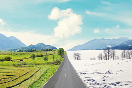 country road through mountainous winter and spring landscape, seasons rotation Stock Photo