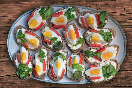 quartered: open-faced sandwiches plated with remoulade, eggs, fresh watercress and red peppers Stock Photo