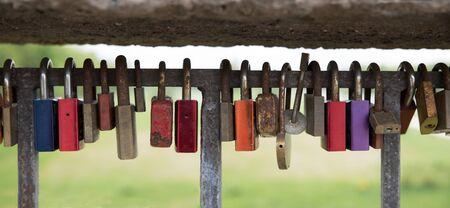 love proof: row of colorful padlocks on a bridge balustrade as a token of love.