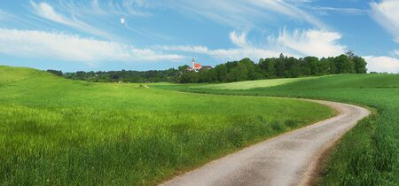 pictorial rural landscape with winding country lane and famous chapel andechs, upper bavaria