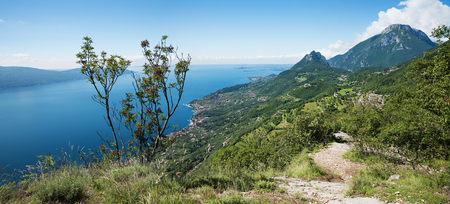 idyllic hiking path above garda lake with beautiful lake view and monte pizzocolo, italy
