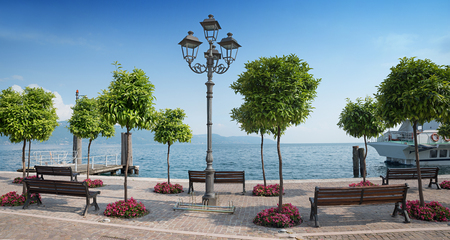 pictorial: pictorial lakeside promenade gargnano, with orange trees and benches, garda lake, italy Stock Photo