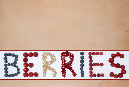 formed: wooden background with text formed with berries - strawberry, raspberry, red and white currant, blueberry Stock Photo