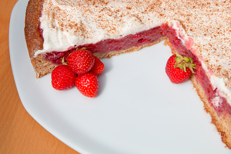 truncated: truncated wholemeal strawberry cake on a plate and fresh berries, wooden table and space for text Stock Photo