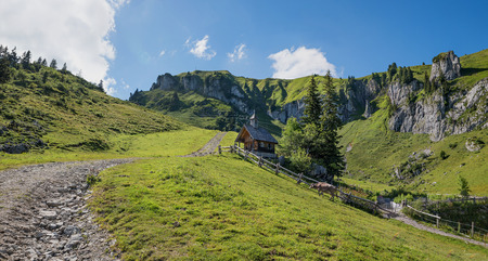 pictorial: pictorial mountain scenery with wooden chapel, garden and milk cow, hiking area brauneck, upper bavaria Stock Photo
