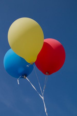 roped: three roped up balloons , blue red and yellow colored, flying in the sky Stock Photo