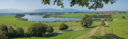 shrubbery: idyllic bavarian landscape with lake riegsee and the mountain range, called the blue land Stock Photo