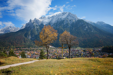 lookout point over mittenwald town, place for meditation and recreation with benches and christian cross, autumnal landscape bavaria