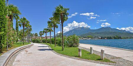 lakeside promenade riva del garda with palm tree alley, north italy