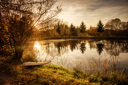 little moor lake at sundown, old surfboard at the shore, autumnal scenery