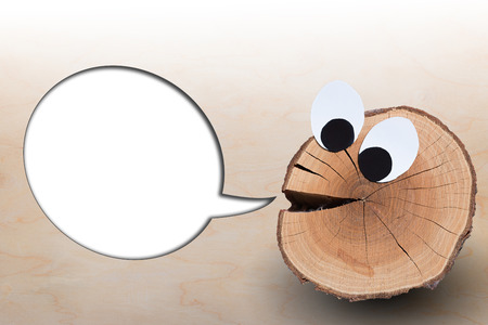 humor: funny face with blank speech bubble on wooden background