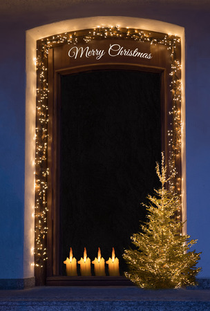web portal: door with fairy lights, christmas tree and candles. background with black textured copy space for text and holiday greeting