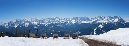 wooden sunbeds at wank mountain summit with lookout to the beautiful zugspitze wintersport area, garmisch-partenkirchen