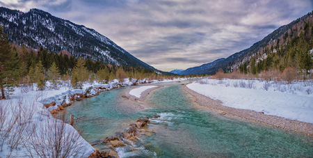 natural site isar river, snow covered, landscape and dramatic sky, at early springtime.