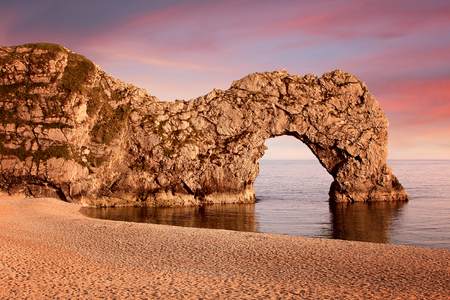sunset at the beach, Durdle Door, coastal landscape Dorset with famous stone arch