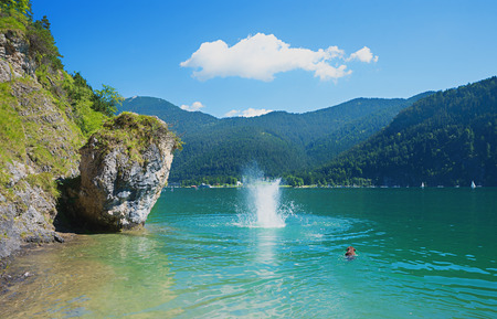 summer fun at lake achensee. dog is crawling in the water while his master jumped from a big rock in the cold water
