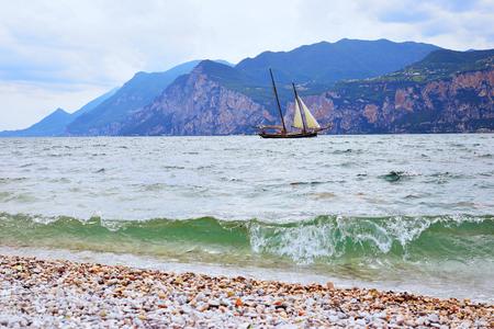 sailing ship at garda lake and lombard mountains, italy