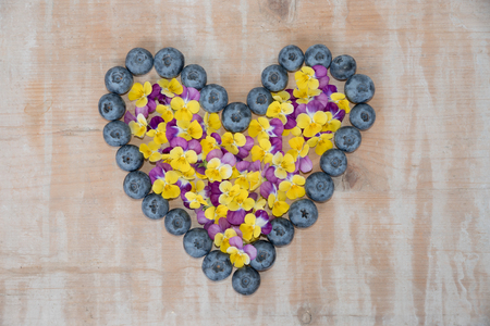 love heart made of big blueberries filled with colorful horned pansy blossoms on wooden background.
