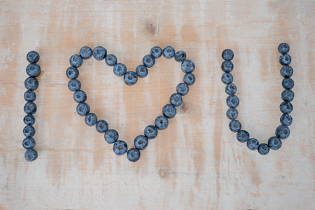 i love you text, formed with big blueberries  on wooden background