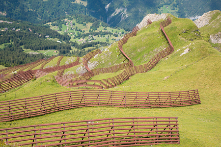 avalanche barrier at mountain meadow. alpine landscape switzerland. Foto de archivo - 116249008