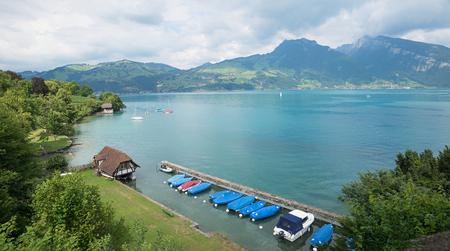 idyllic bathing beach spiez, lake thun, with moored boats and mountain view Stock Photo