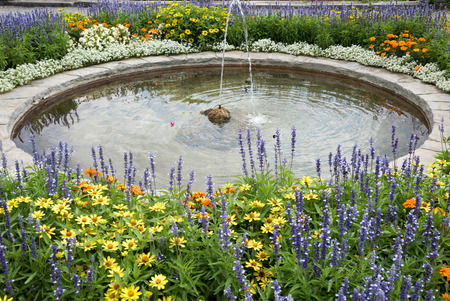waterspout fountain framed with colorful flowers. yellow zinnias, orange calendula and blue sage blossoms