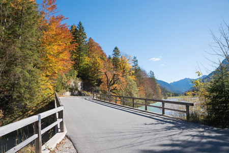 country road through nature preserve karwendel, risstal valley in autumn. 스톡 콘텐츠