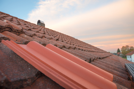 house roof closeup, old roofing and one new tile. replacement of defect roof tiles.