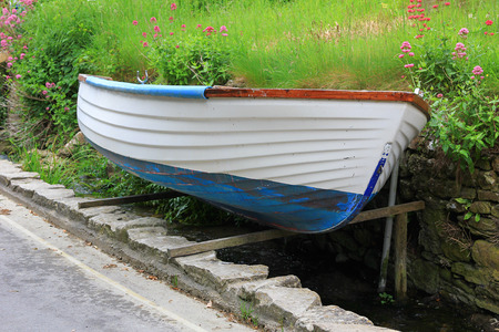 jacked up rowing boat beside the street, green grass background with flowers