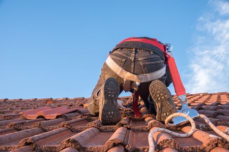 worker at the rooftop, with security equipment, replacing old roof tiles. blue sky with copy space.