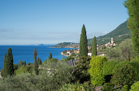view to gargnano village and shore of garda lake, mediterranean vegetation. beautiful tourist resort italy in summer. blue sky with copy space.