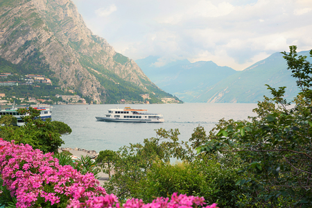 passenger liner en route to limone village, garda lake italy. with pink geranium flowers