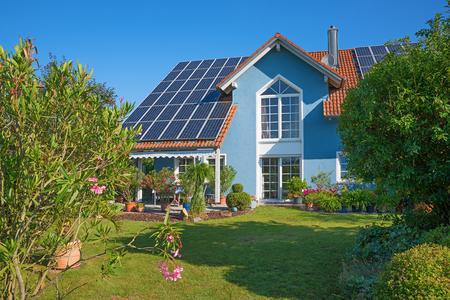 Hinterhofgarten eines schönen Einfamilienhauses mit Sonnenkollektoren auf dem Dach und idyllischem Garten mit mediterranen Pflanzen