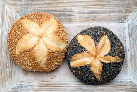 sesame roll and poppy seed roll in a wooden basket, star shaped mark in the middle of the buns Imagens