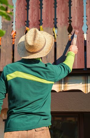 gardener with straw hat, renovating wooden balcony balustrade with brown artists color