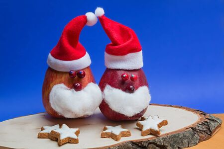 christmas decoration with two funny santa clause apples and cinnamon stars on a wooden tree slice, blue background with copy space