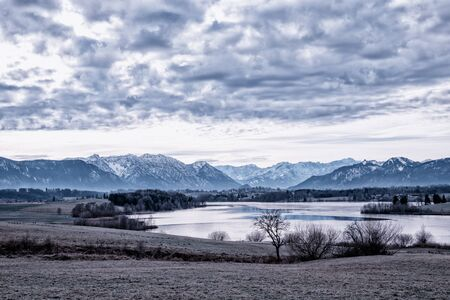 frosty morning scenery in the bavarian region Blaues Land, view to lake riegsee, grey clouds and landscape at wintertime