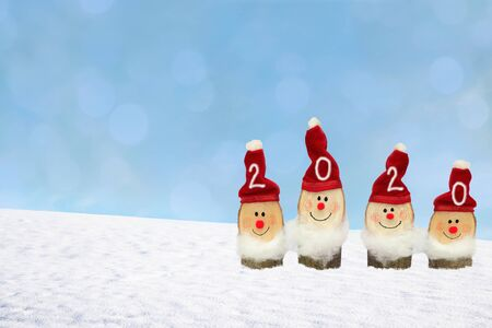 wintry background with four smiling santa gnomes and snowy hill, year 2020 and blank space for text. festive handicrafts work