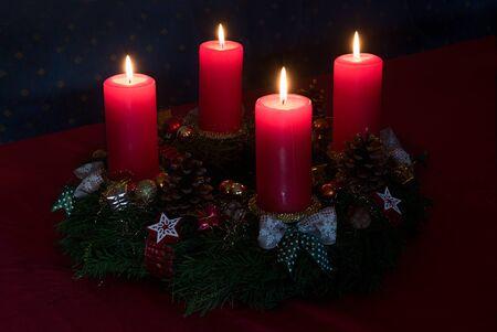 Adventskranz mit vier brennenden roten Kerzen auf rubinroter Tischdecke, stimmungsvolle Weihnachtskulisse zu Hause Standard-Bild