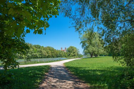 idyllic walkway at riverside of Isar river in munich, recreational area in the city, summer landscape