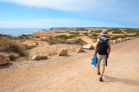 hiker on bumpy coastal road near Carrapateira, dune landscape West Algarve Portugal. view to the atlantic ocean Stock fotó
